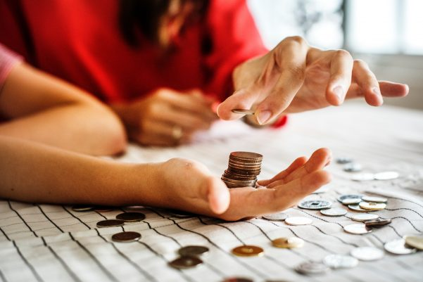 Two people counting pennies on a table