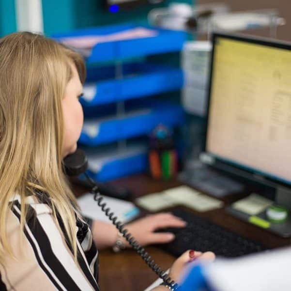 WFP Service Desk Staff answering the phone to a customer in front of a computer screen