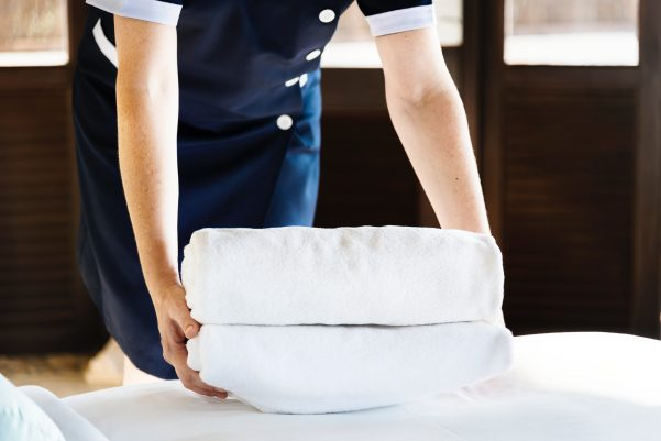 Maid laying towels on a bed in a hotel