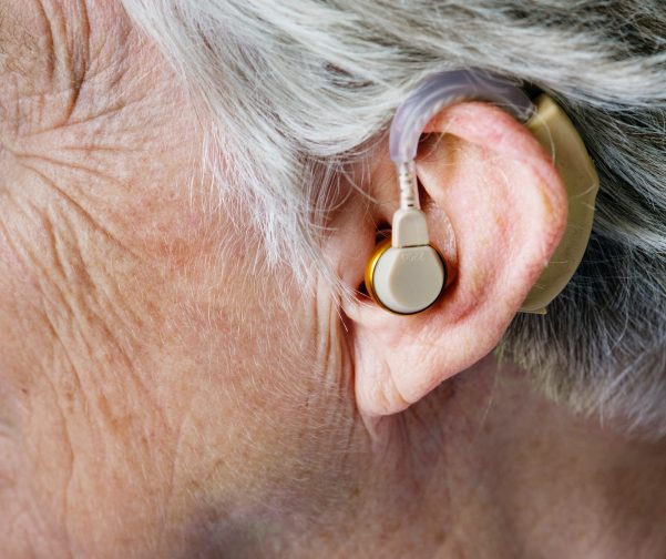 Close-up of a senior person's ear with a hearing aid
