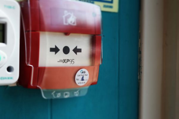 Manual Call Point on a wall with WFP sticker on it with the Number 1