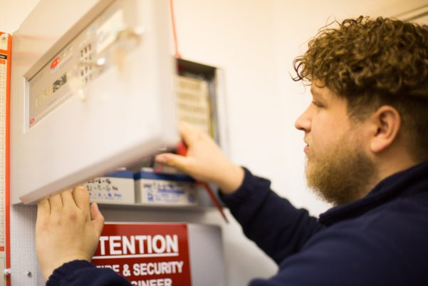 Fire alarm engineer working on a fire alarm panel