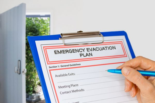 Clipboard saying 'Emergency Evacuation Plan' with a hand holding a pen ready to write
