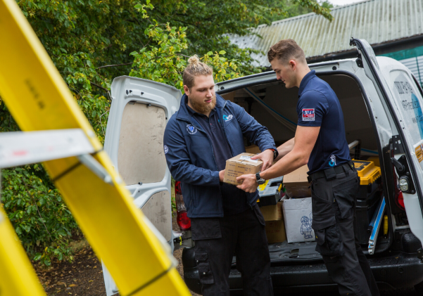 Two WFP engineers at the back of a van handing a device to one another with a ladder in view