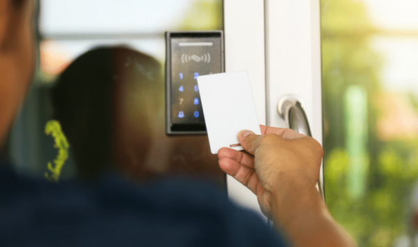 Hand with key card against access control system to permit entry at a doorway