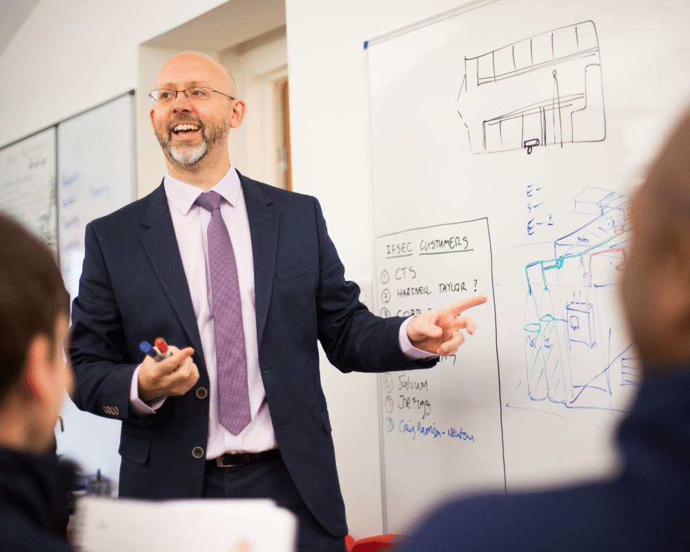 Managing Director Paul Field pointing at whiteboard