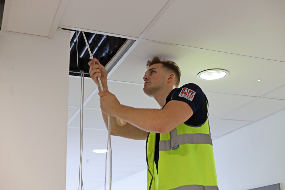 WFP Engineer in a high vis vest pulling a wire out of a ceiling