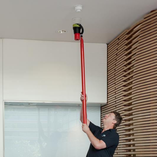 Fire alarm engineer using a smoke pole to test a smoke detector during fire alarm maintenance