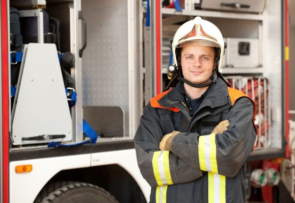 Firefighter in front of a fire brigade truck smiling at the camera