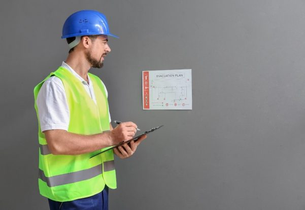 Man in high vis with a blue helmet holding a clipboard and looking at an evacuation plan on the wall as part of a Fire Risk Assessment